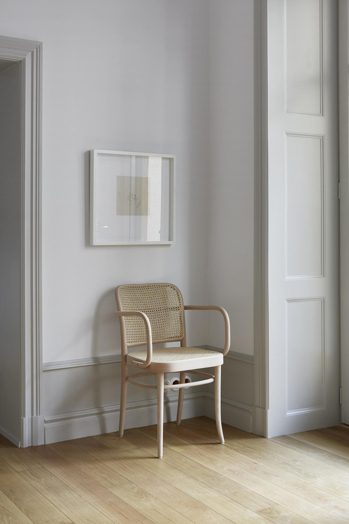 Serene Stockholm apartment with bentwood chair and framed art
