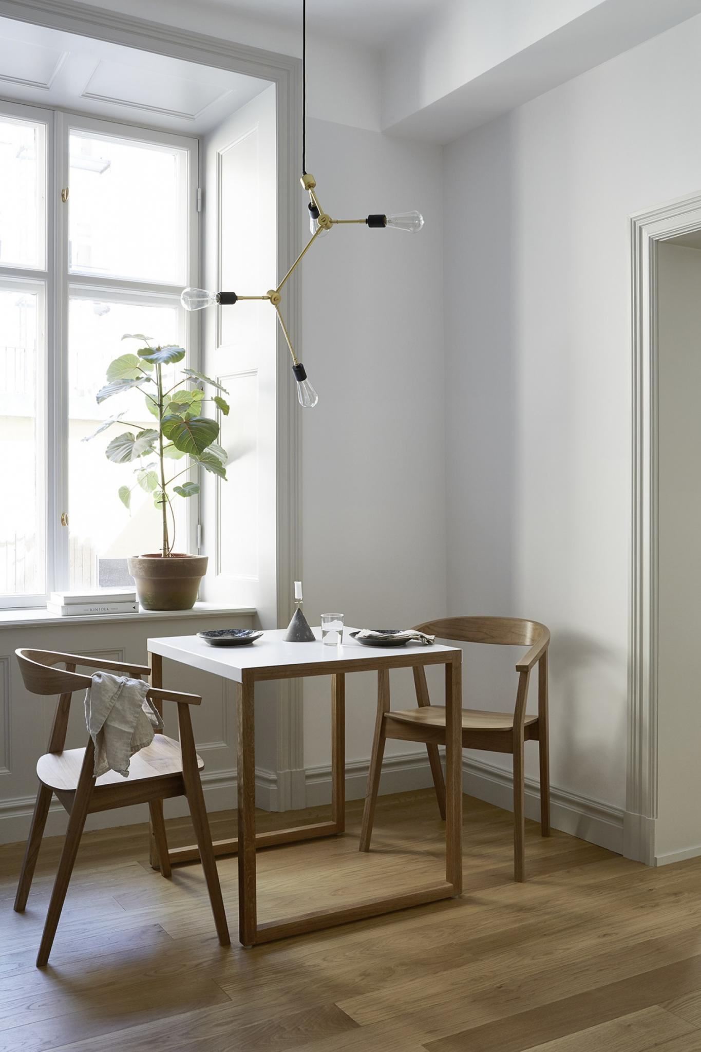 Modern Scandinavian wood chairs and table with modern brass hanging pendant in Stockholm apartment
