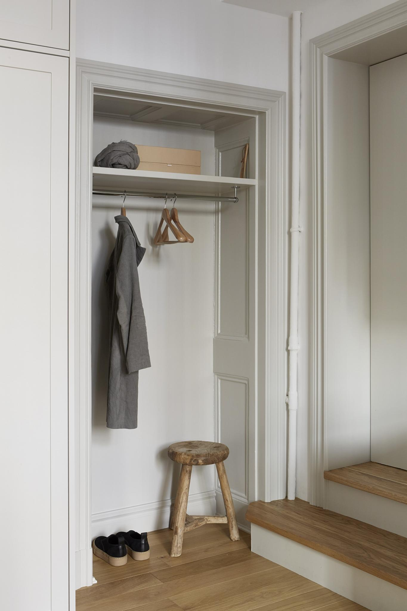 Closet with no door and rustic three legged wood stool in Stockholm apartment