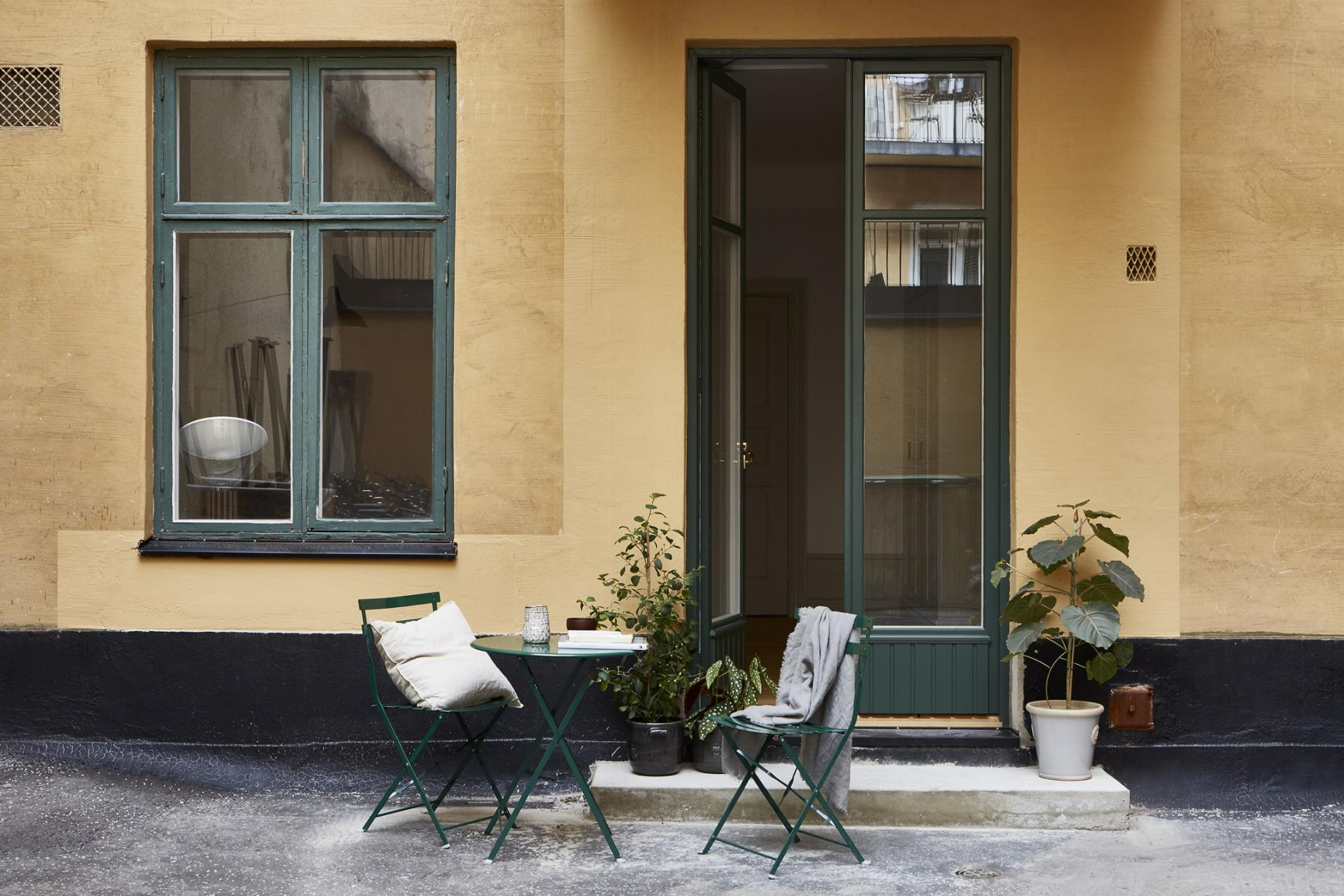 Deep green trim on yellow stucco Stockholm apartment with bistro set outdoors