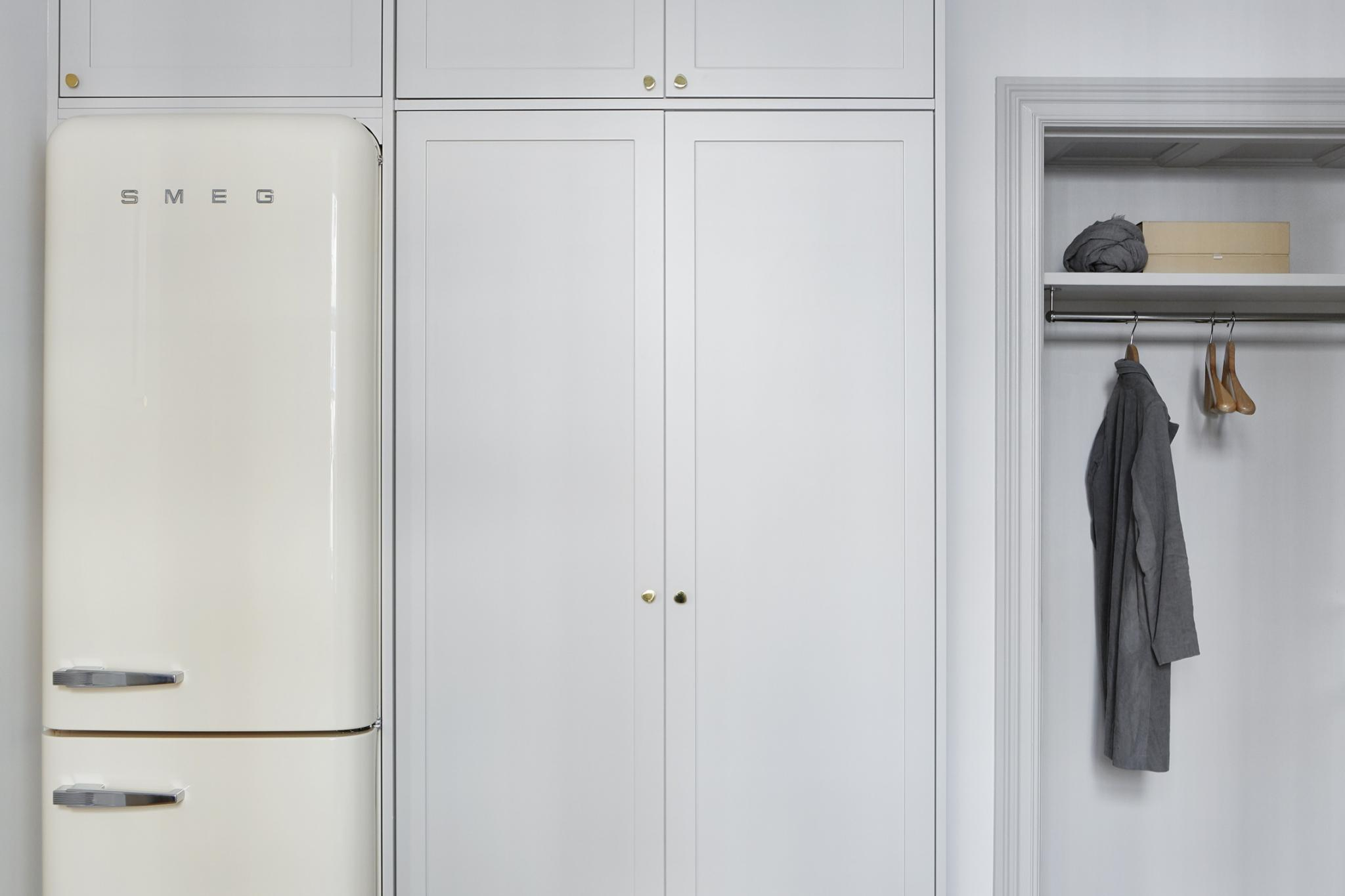 Charming Smeg frig built into cabinetry in small Stockholm apartment